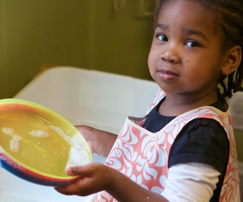 A 3-year-old African American girl looks up with a satisfied expression from her dishwashing work. She is wearing a floral-print apron and holding a dish in her hand.